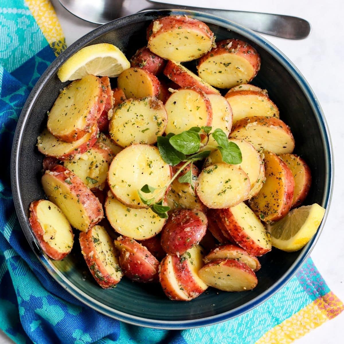Bowl of Greek potato salad garnished with a sprig of fresh oregano