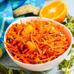 Bowl of carrot and orange salad surrounded by sprigs of fresh cilantro and mint