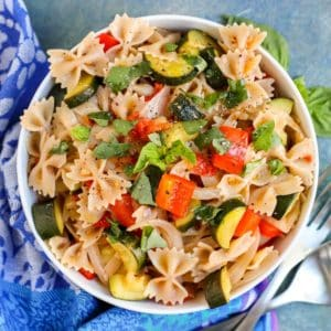 Bowl of farfalle pasta with roasted vegetables and fresh basil