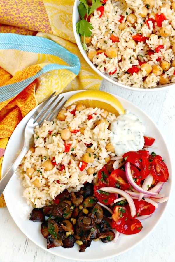 Rice with chickpeas on a plate with roasted mushrooms, tomato onion salad, and yogurt sauce
