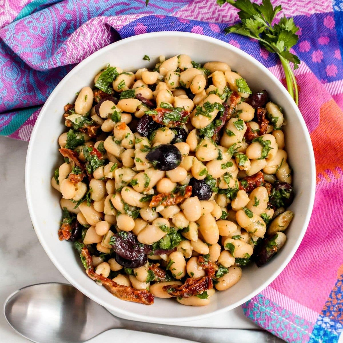 Bowl of white bean salad with olives and sun-dried tomatoes