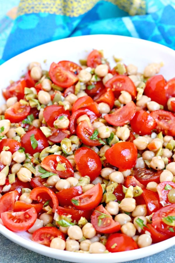 Close up of chickpea and cherry tomato salad tossed with green olive dressing