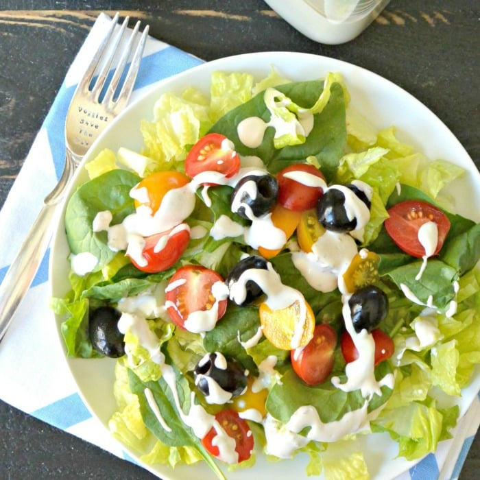 Salads with olives and tomatoes topped with cashew ranch dressing