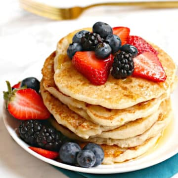 Stack of pancakes topped with fresh berries on a white plate with a gold fork in the background