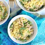 Overhead of bowls of lemon orzo with asparagus and chickpeas with a blue napkin
