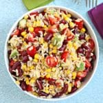 Overhead of bowl of brown rice salad with kidney beans, avocado, corn, and tomatoes