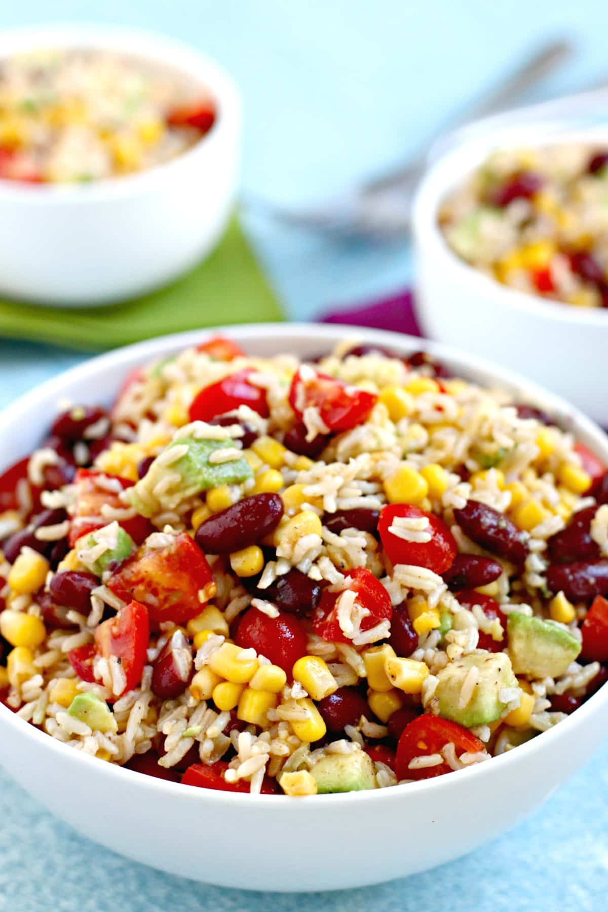 Close up of bowl of Southwestern brown rice salad with corn, kidney beans, tomatoes, and avocado
