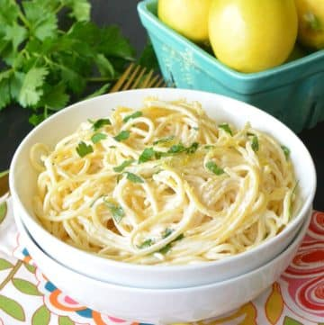 White bowl containing Lemon Dairy Free Pasta Sauce with aqua basket of lemons and parsley in the background