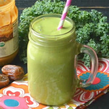 Green smoothie in a mason jar with a pink straw and a bunch of kale in the background