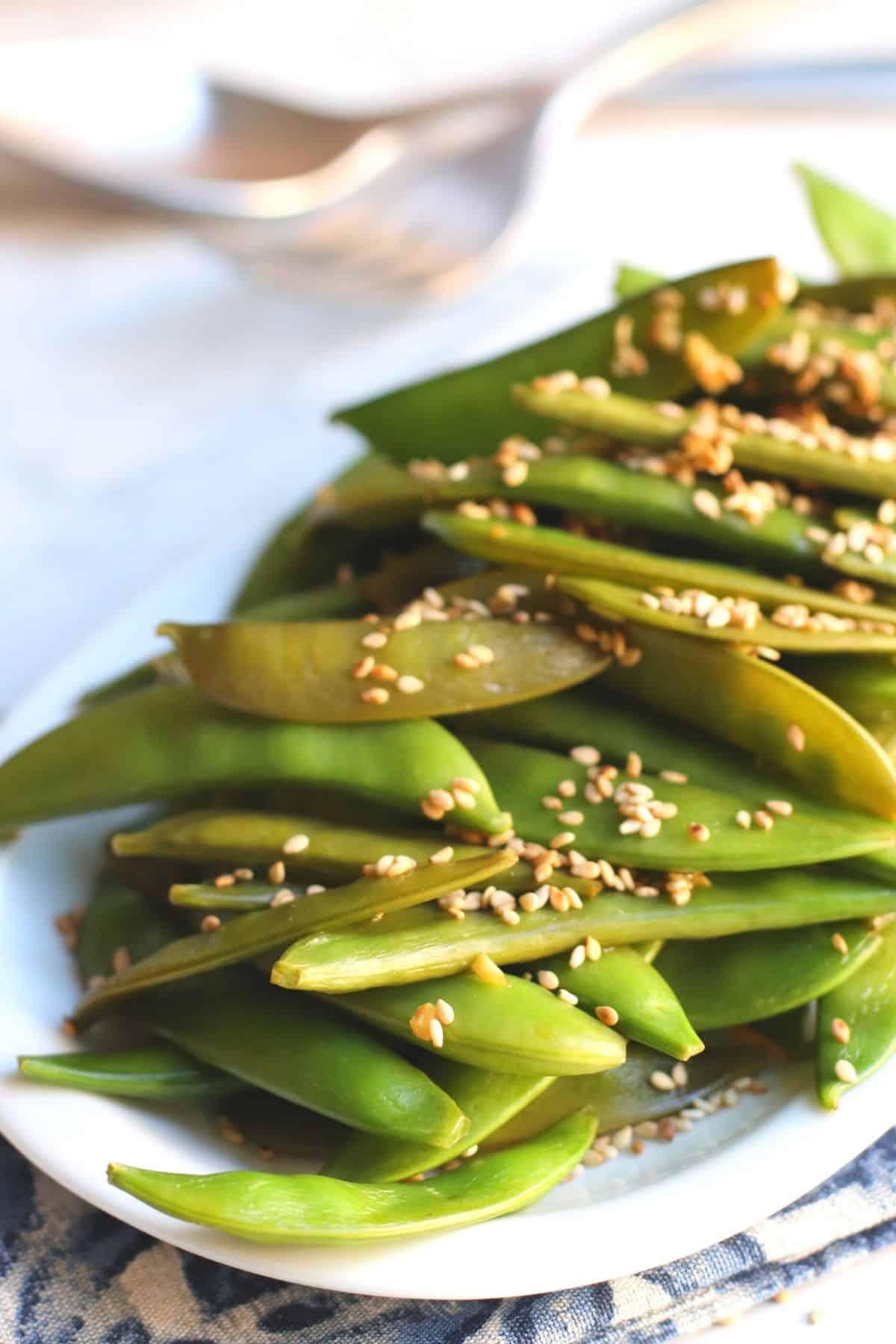 Platter of stir fried snap peas garnished with toasted sesame seeds