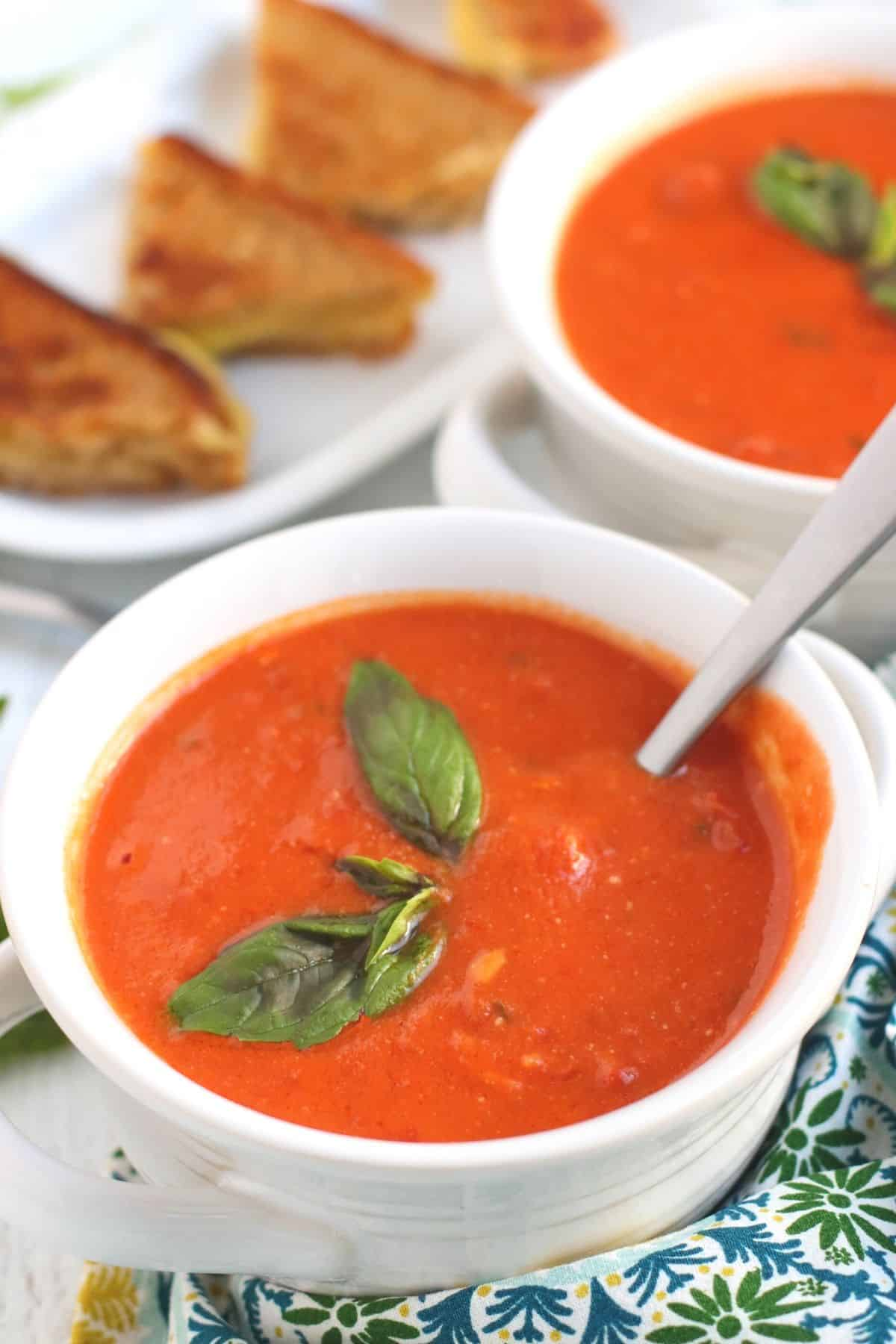 White bowls of creamy vegan tomato soup garnished with fresh basil with plate of grilled cheese sandwiches in the background