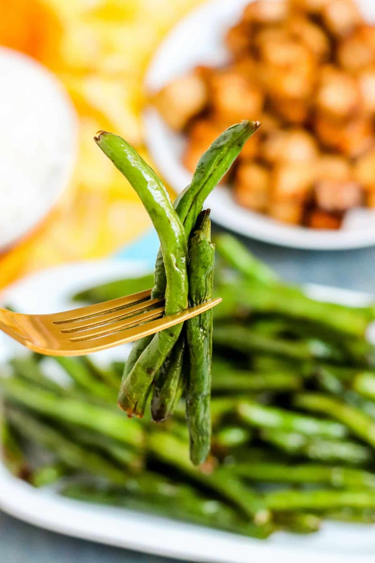 Close up photo of green beans on a gold fork