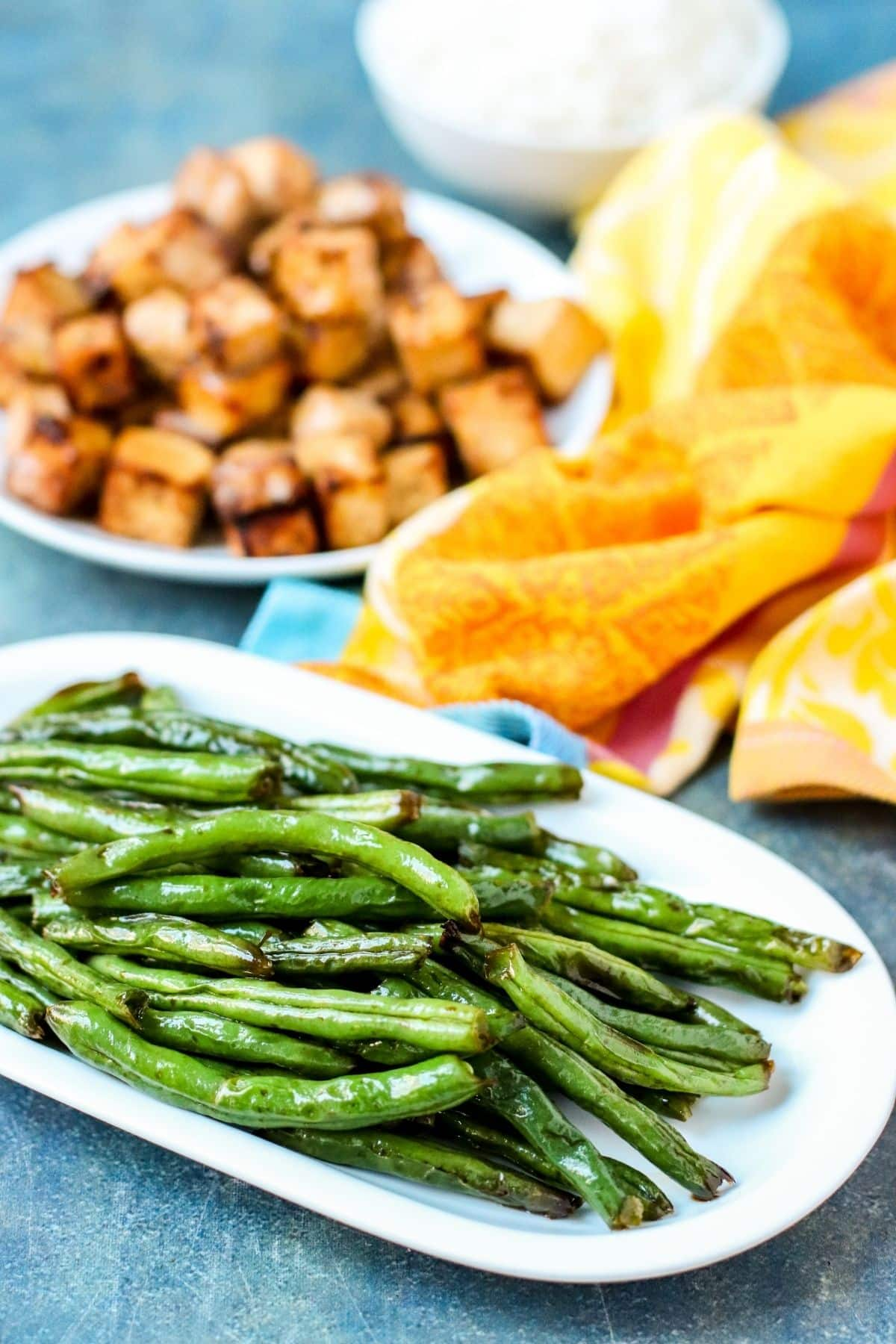 Platter of air fryer green beans with plate of tofu and bowl of rice in the background