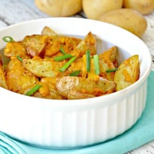 Serving bowl of potato wedges topped with cheesy sauce