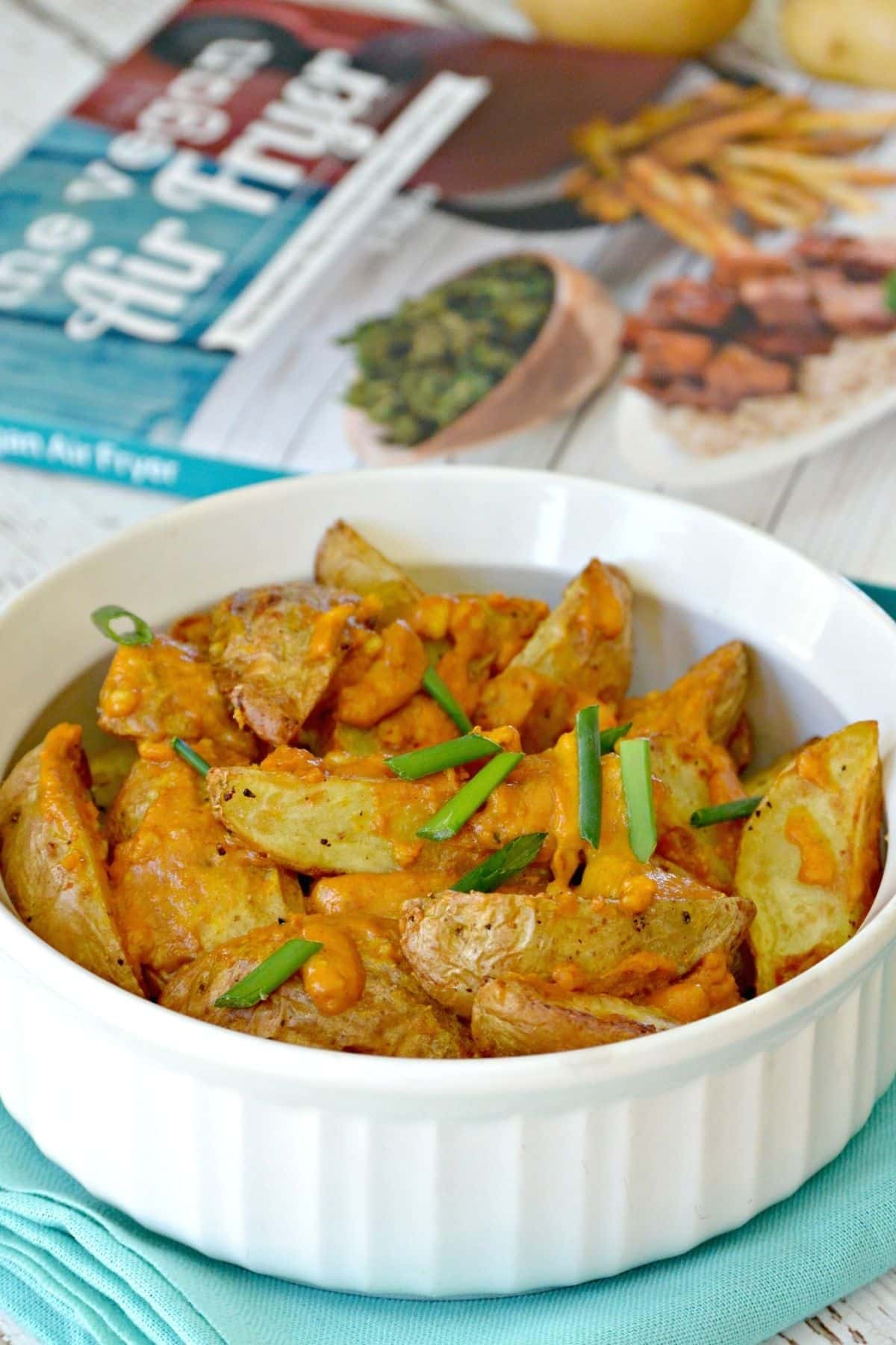 Bowl of wedges topped with sauce and chives with a cookbook in the background