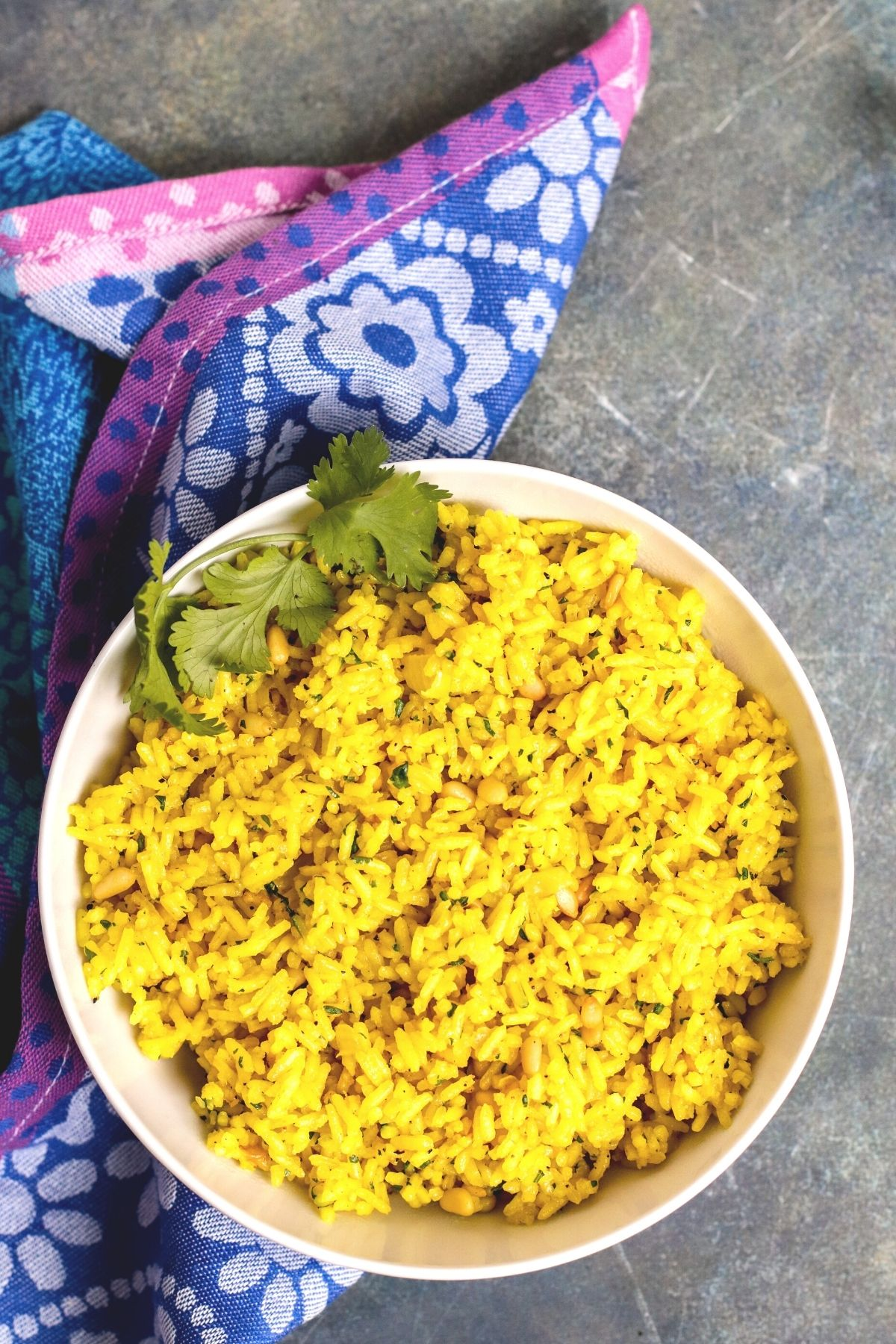 Overhead of bowl of turmeric rice and blue floral napkin