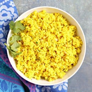 Bowl of turmeric rice garnished with fresh cilantro
