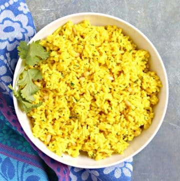 Bowl of turmeric rice garnished with fresh cilantro