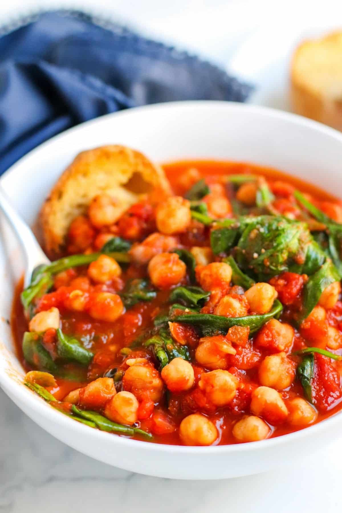 Closeup of bowl of chickpea stew with a spoon in it