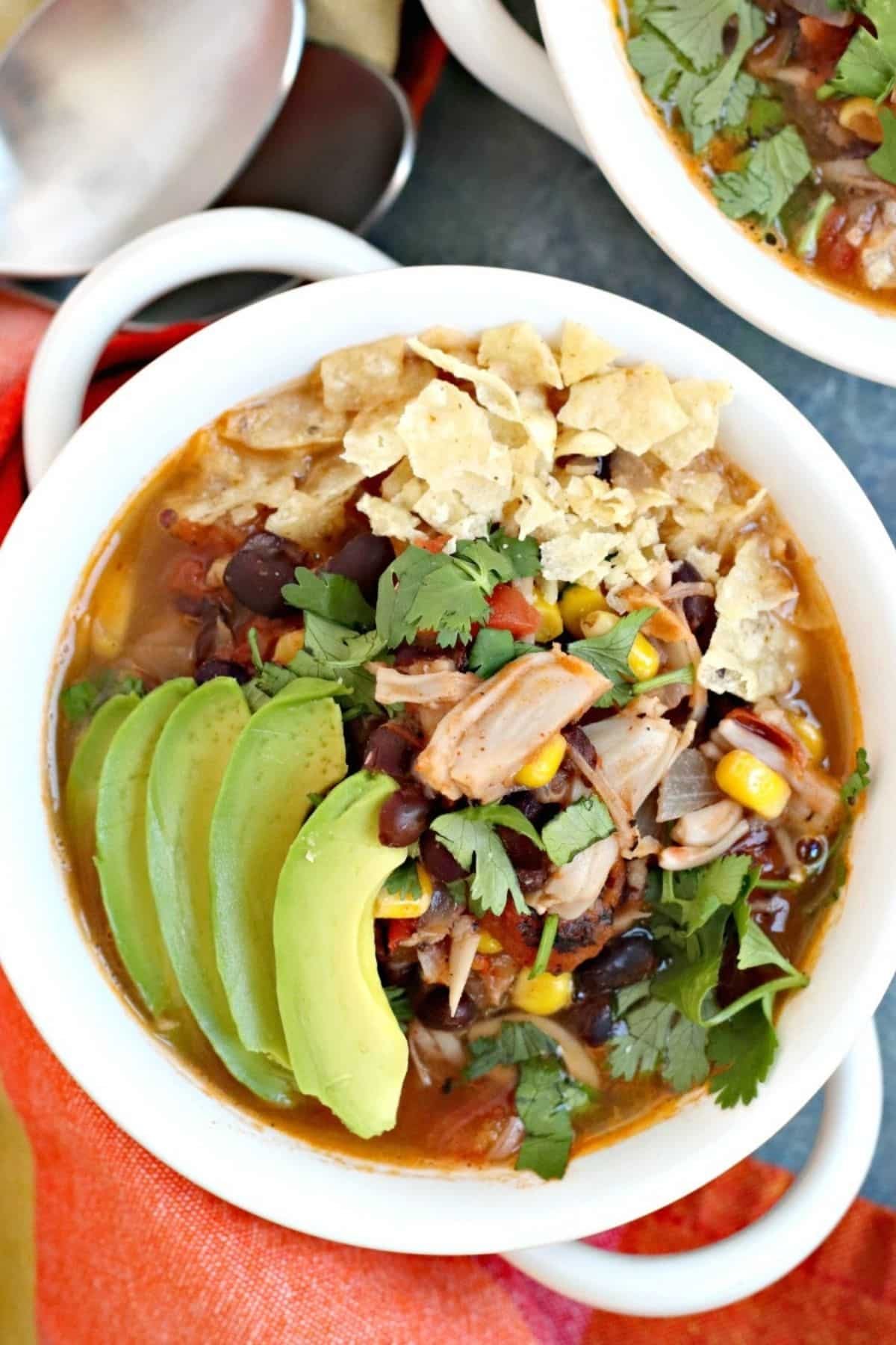 Close up of bowl of taco soup topped with avocado slices, fresh cilantro, and broken tortilla chips