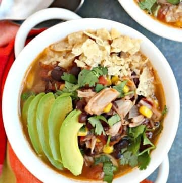 Bowl of soup topped with avocado slices, cilantro, and crushed tortilla chips