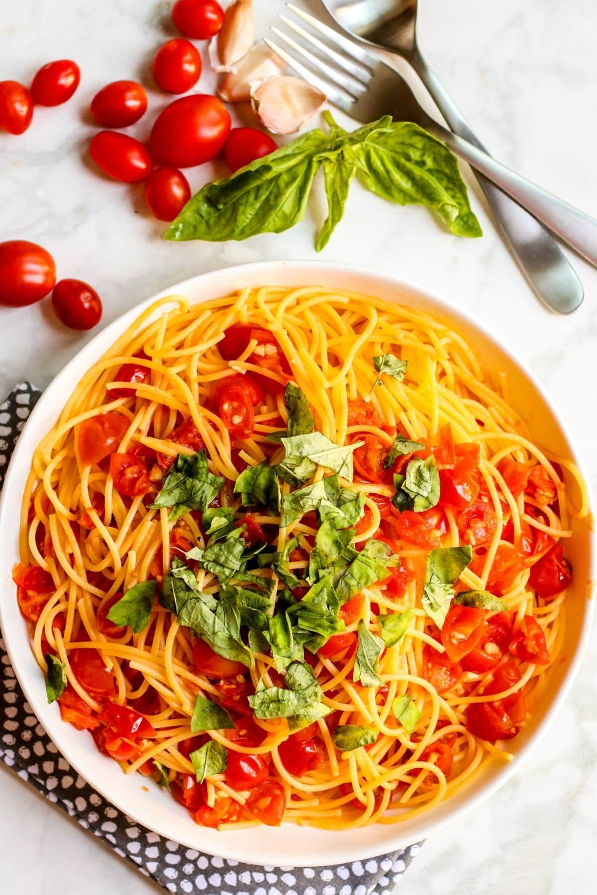 Overhead of a bowl of Angel Hair Pomodoro topped with freshly torn basil leaves