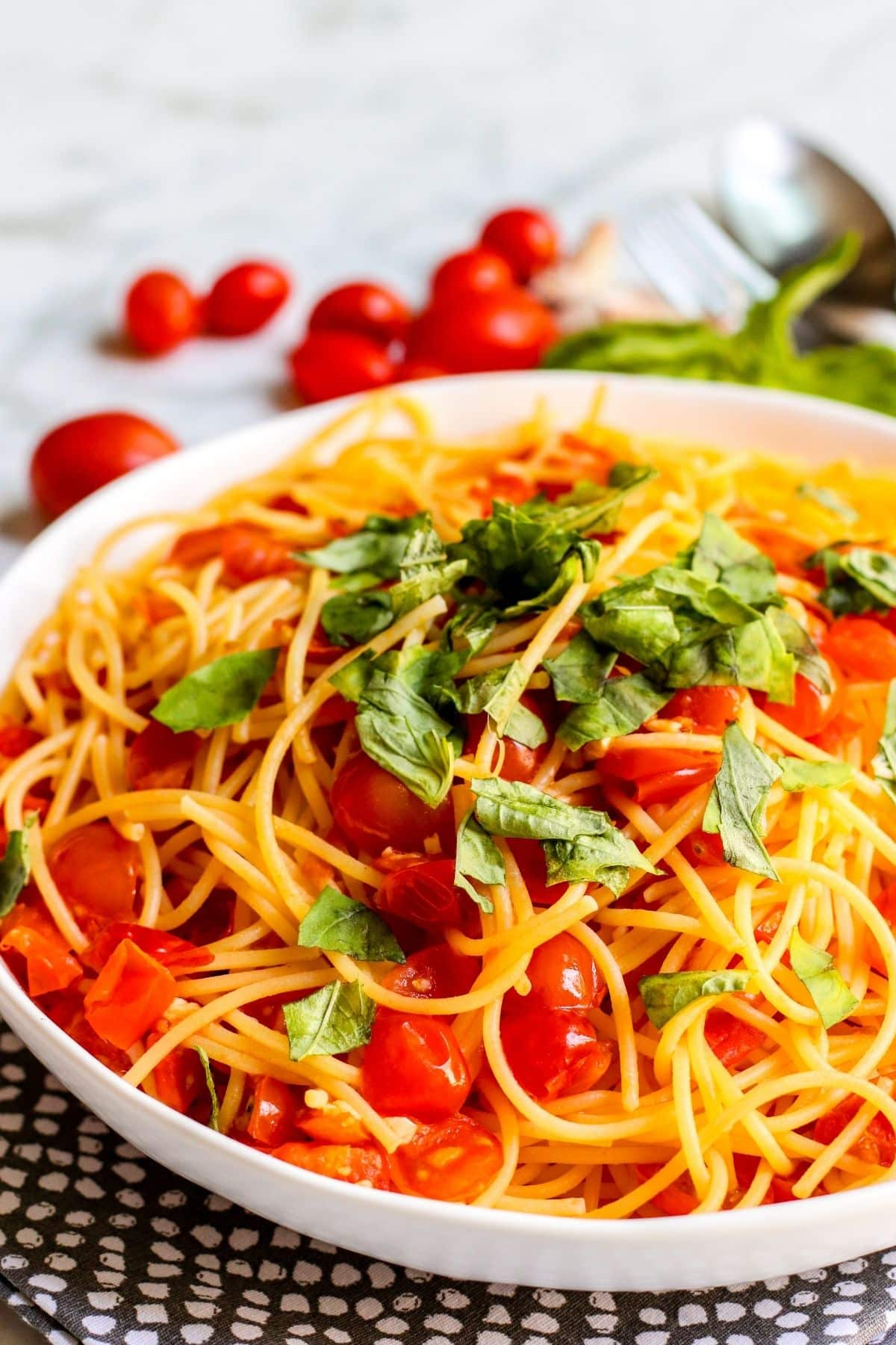 Close up of serving bowl of pasta pomodoro topped with fresh basil