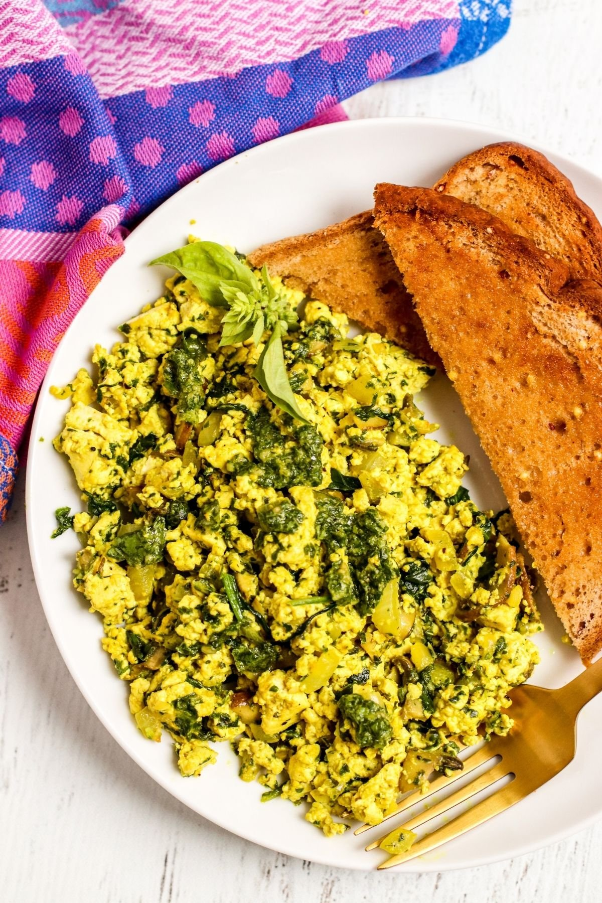 Overhead of plate with pesto scrambled tofu and toast with gold fork and purple napkin