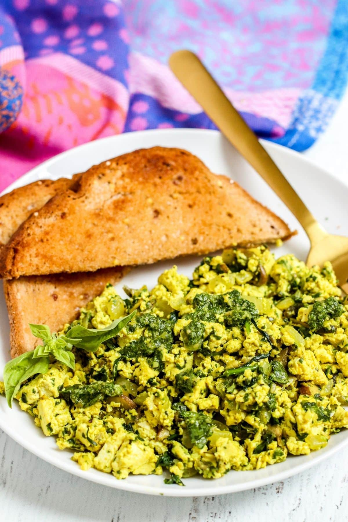 Close up image of finished scrambled tofu topped with pesto with toast on the side