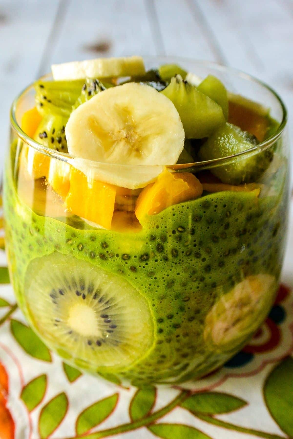 Green chia seed pudding in a clear glass layered and topped with sliced kiwi, mango, and banana