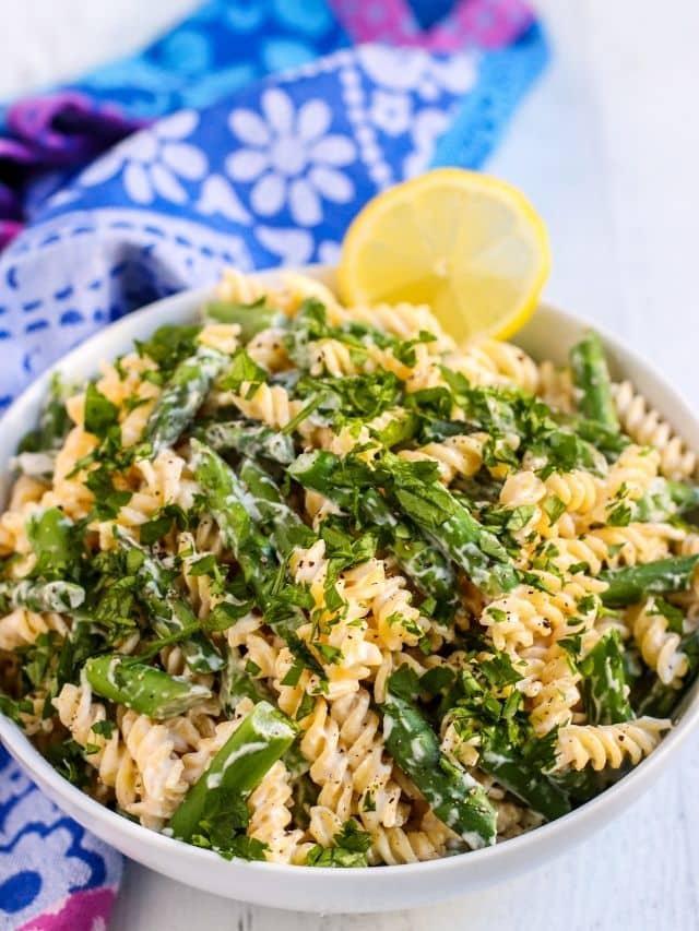 Bowl of asparagus pasta garnished with a lemon slice