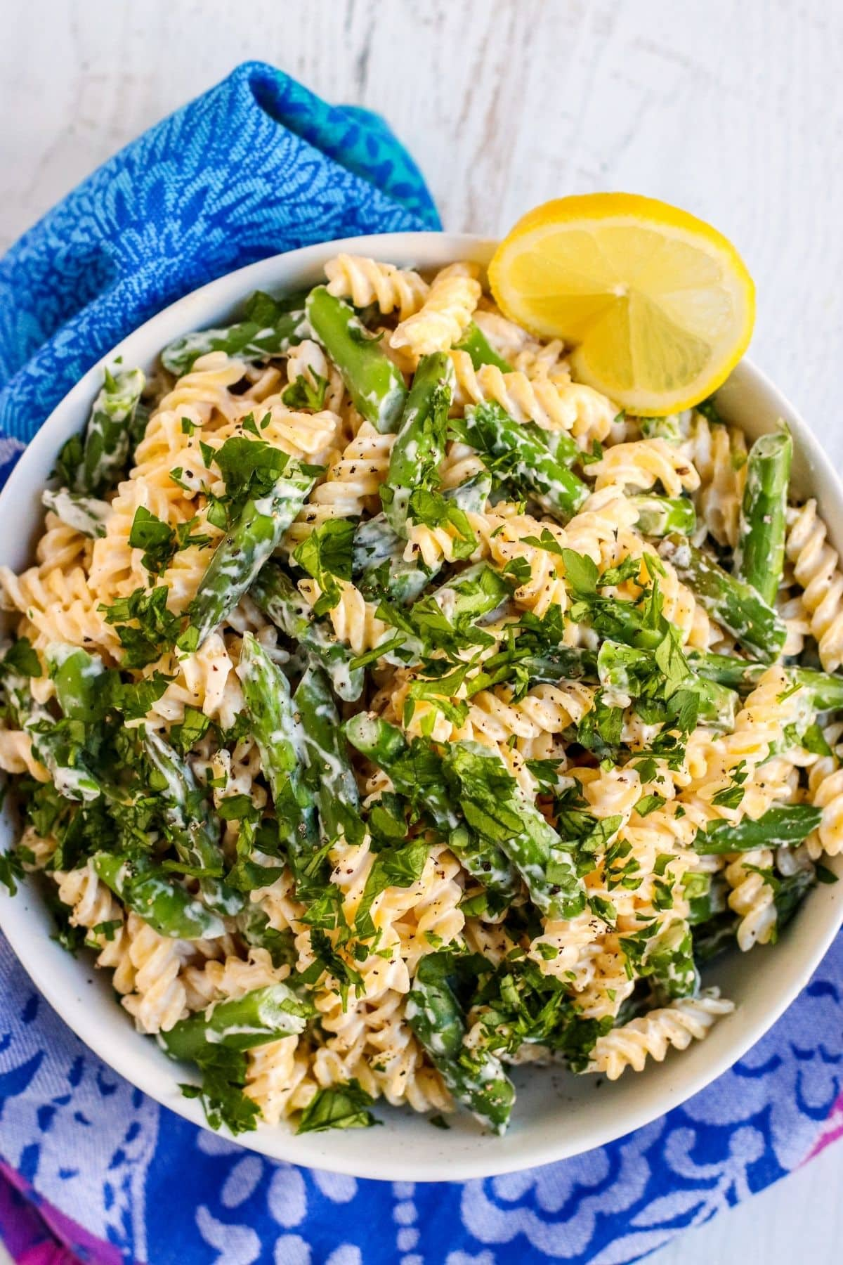 Bowl of asparagus pasta garnished with a lemon wedge