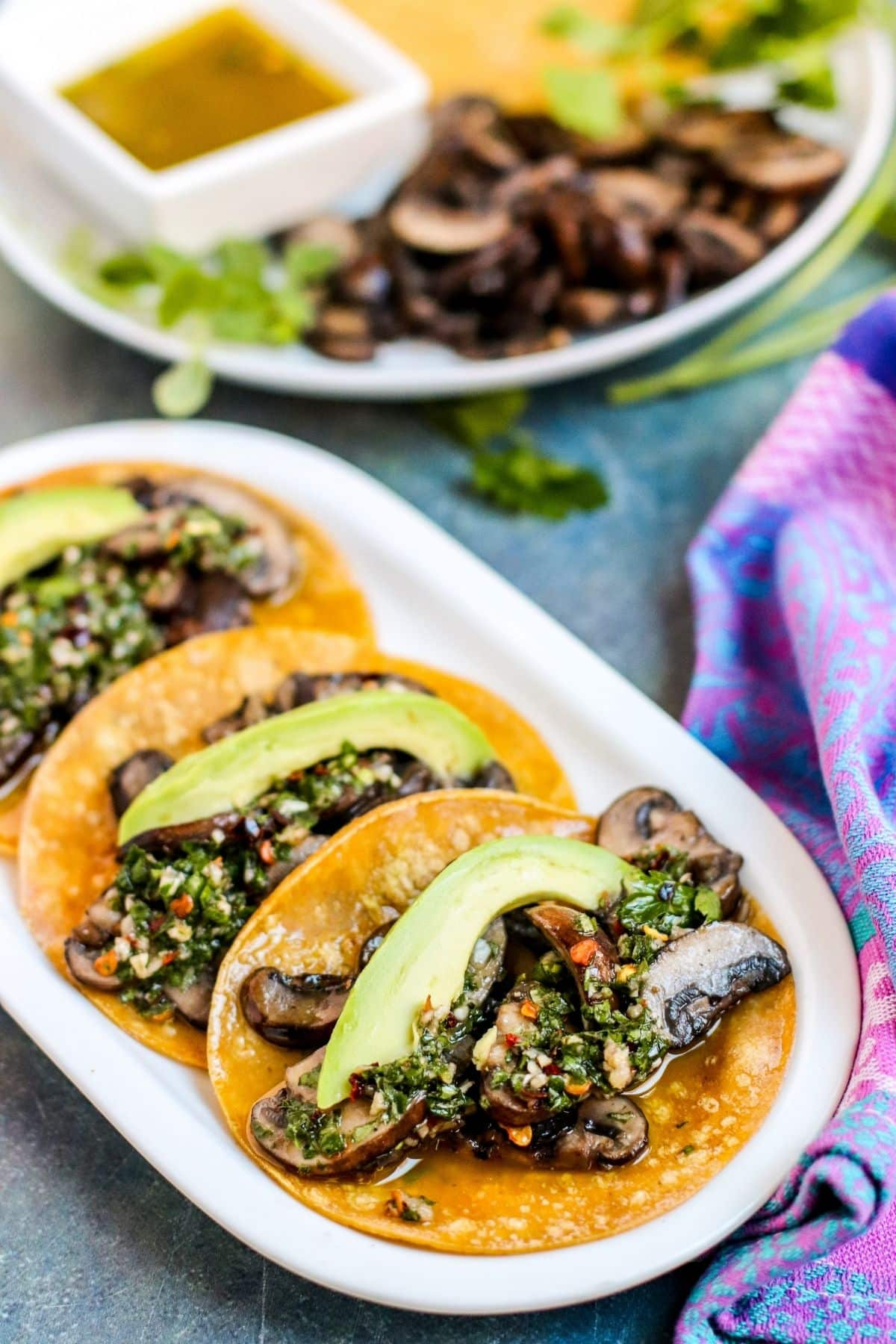 Plater of mushroom tacos topped with avocado slices and Chimichurri sauce