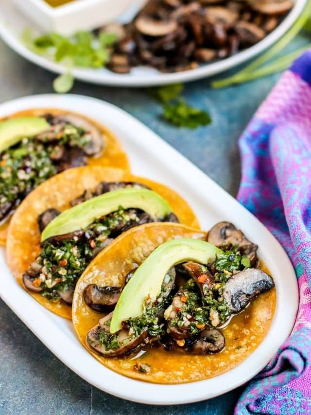 Mushroom tacos topped with avocado slices and Chimichurri sauce on a platter