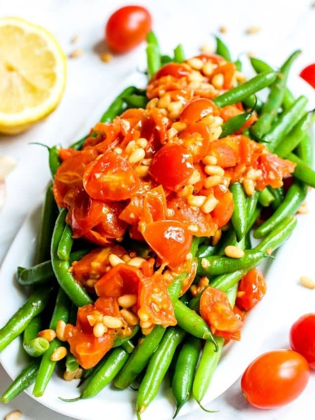 Platter of green beans topped with sauteed tomatoes and pine nuts