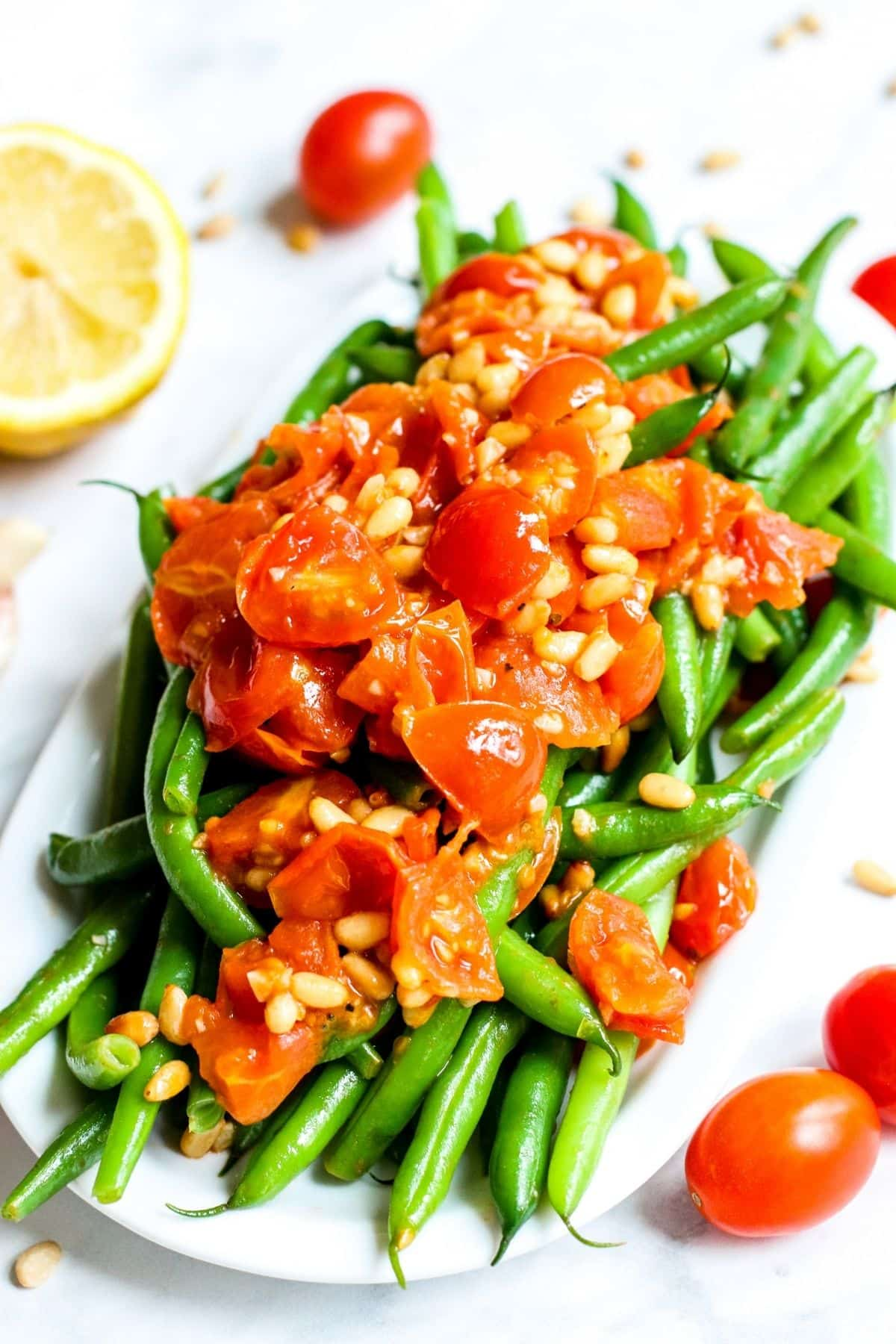 Platter of green beans topped with cooked cherry tomatoes and pine nuts with a cut lemon in the background