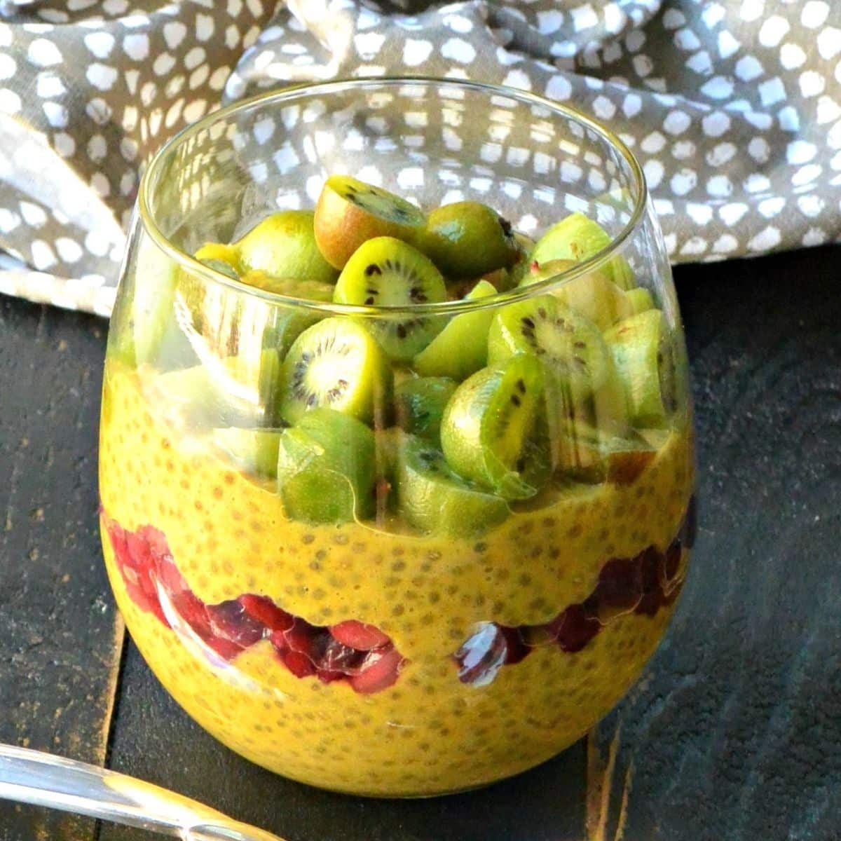 Pumpkin pie chia pudding in a glass layered with pomegranate seeds and topped with kiwi berries