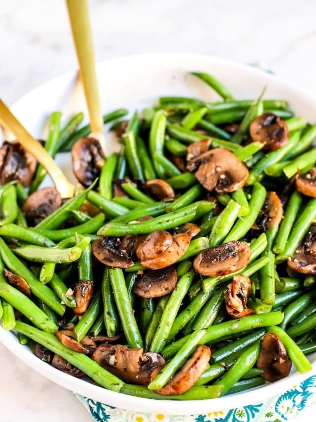 Bowl of sauteed green beans and mushrooms with gold serving utensils