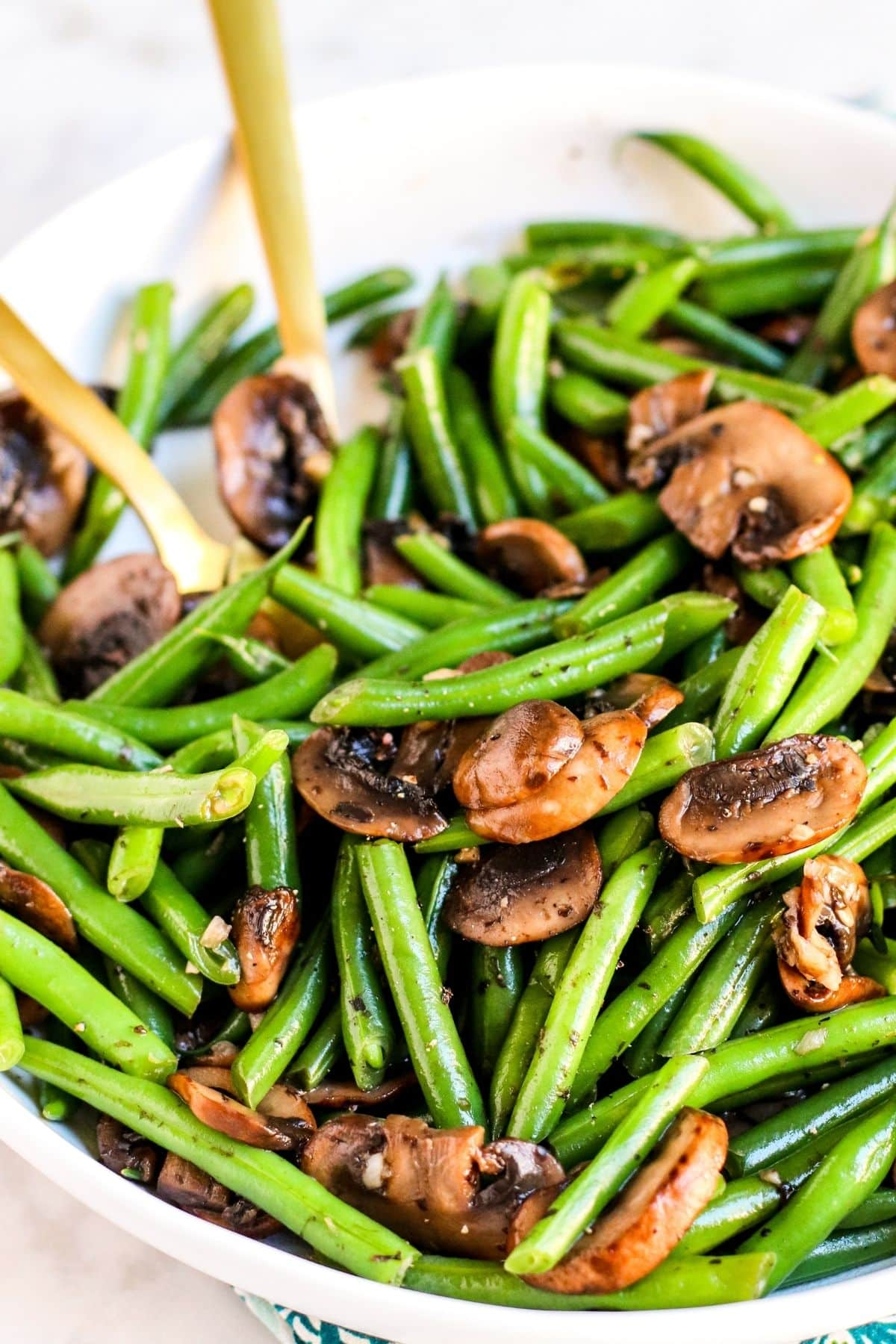 Bowl of green beans and mushrooms with gold serving utensils