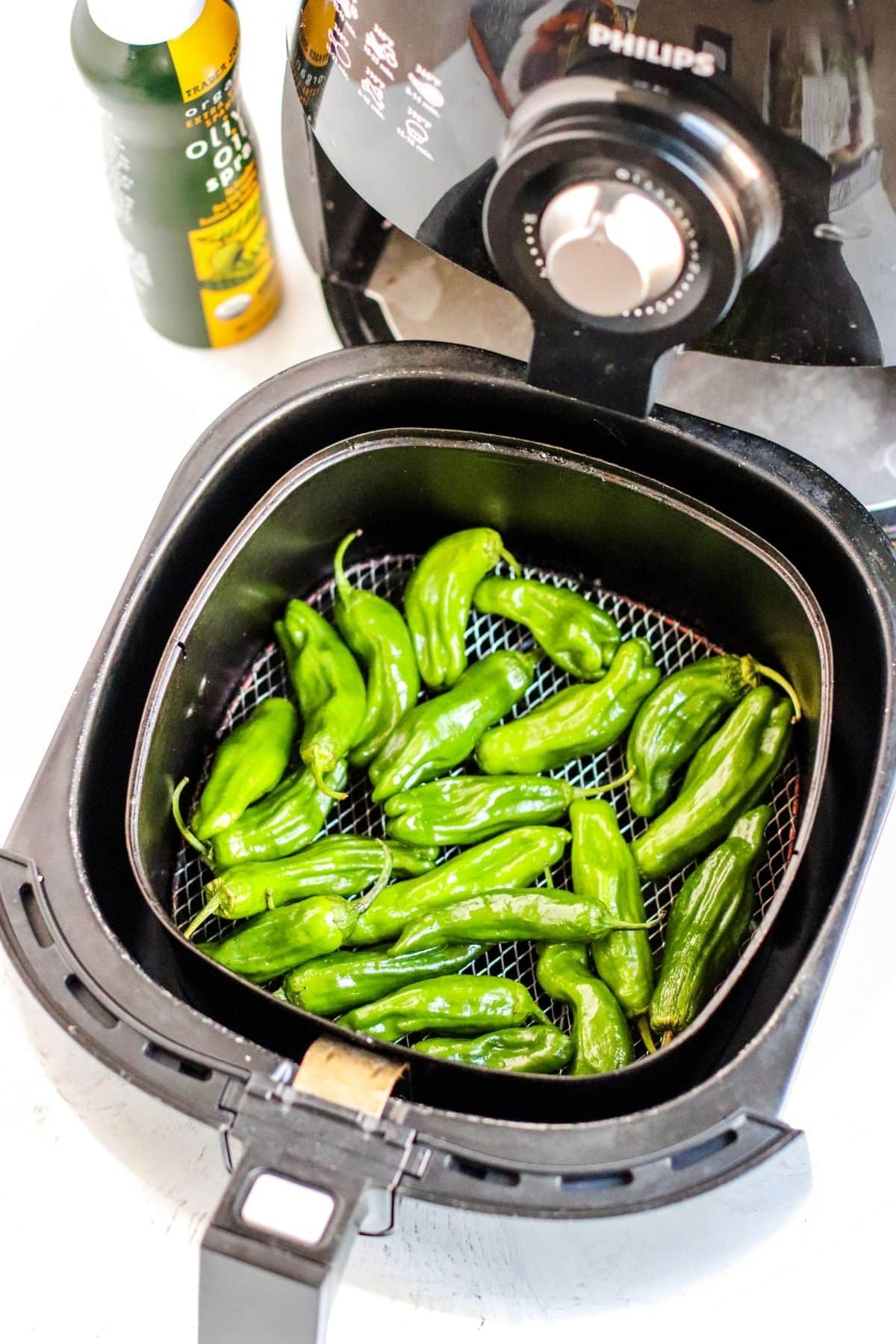 Pepper in an air fryer basket with bottle of olive oil spray next to it