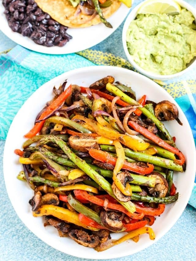 Platter of veggie fajitas with bowl of guacamole and prepared fajitas with black beans on the side