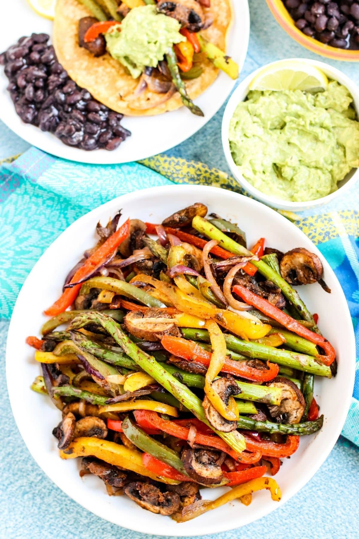 Overhead of platter of veggie fajitas with bowl of guacamole and dinner plate on the side