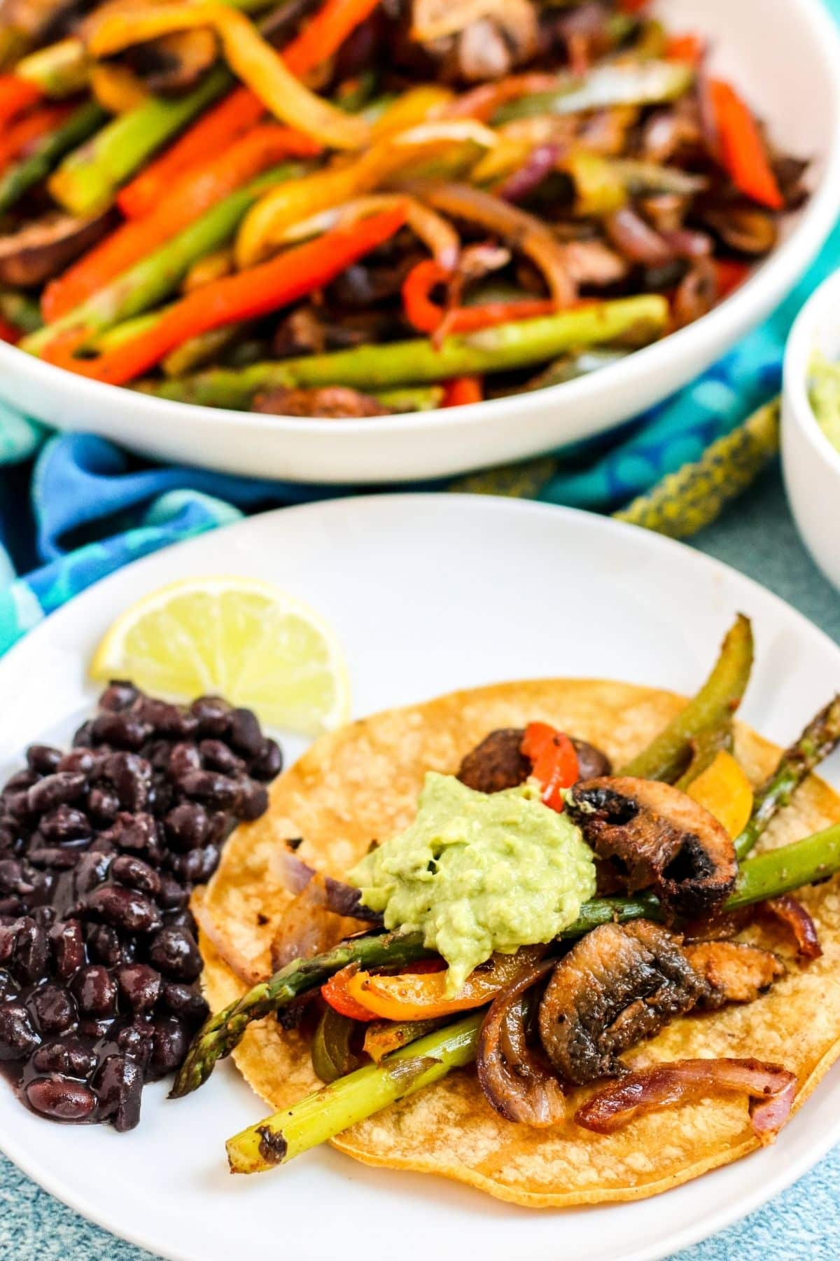 Plate with fajitas on a corn tortilla topped with guacamole and a side of black beans