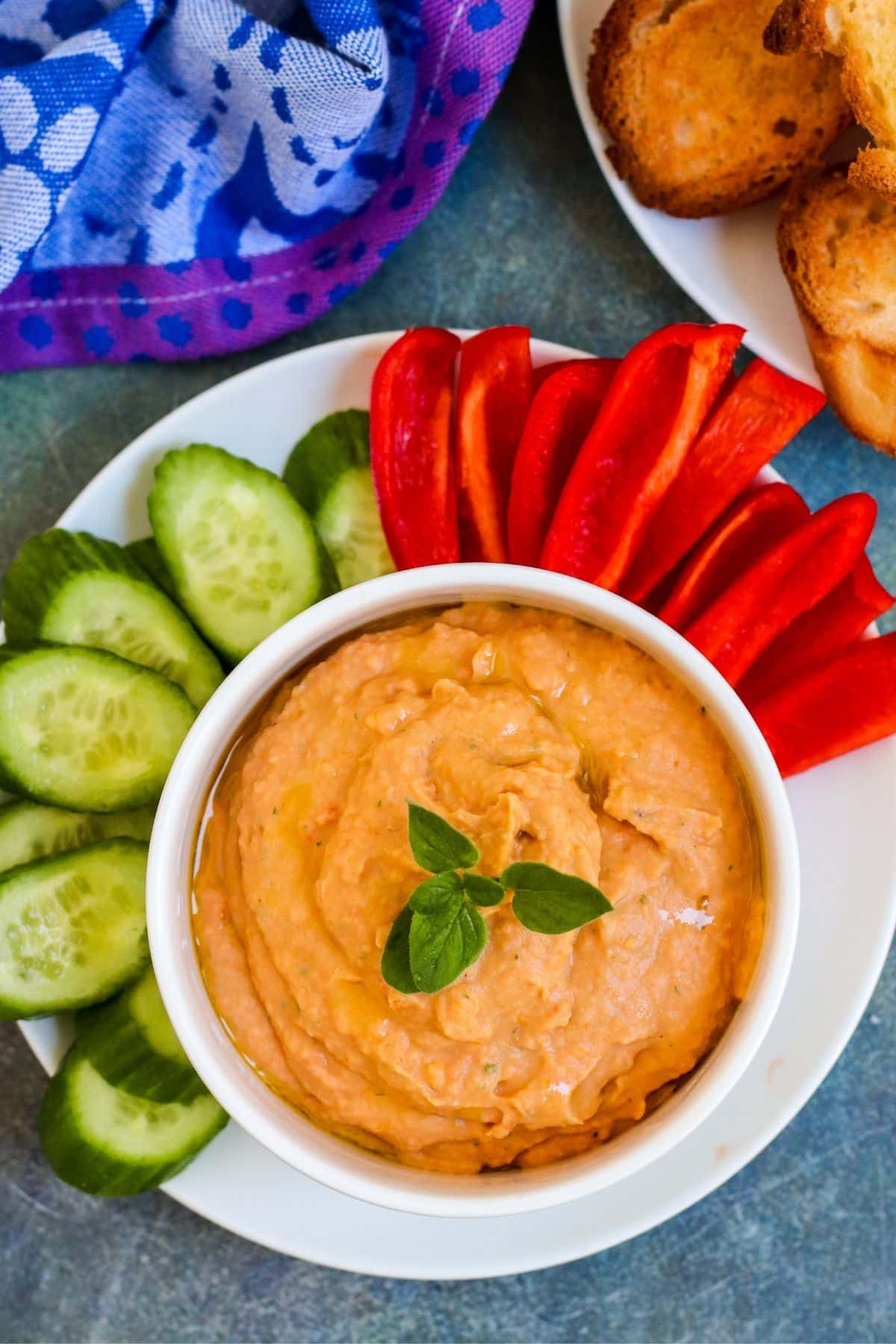 Plate with cucumber slices and strips of red bell pepper around a bowl of sun-dried tomato dip