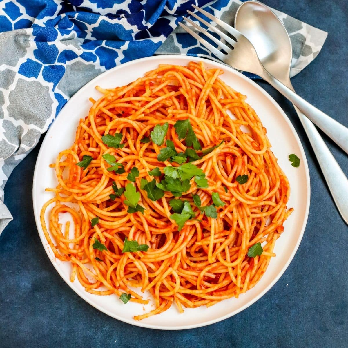 Bowl of spaghetti and tomato sauce garnished with fresh herbs