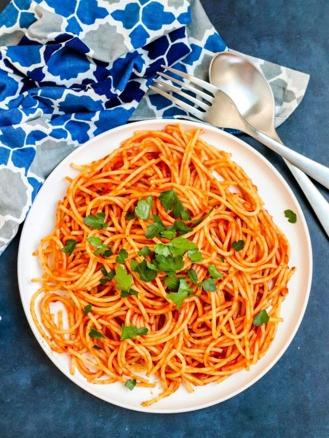 Bowl of spaghetti tossed with tomato paste pasta sauce and garnished with fresh parsley