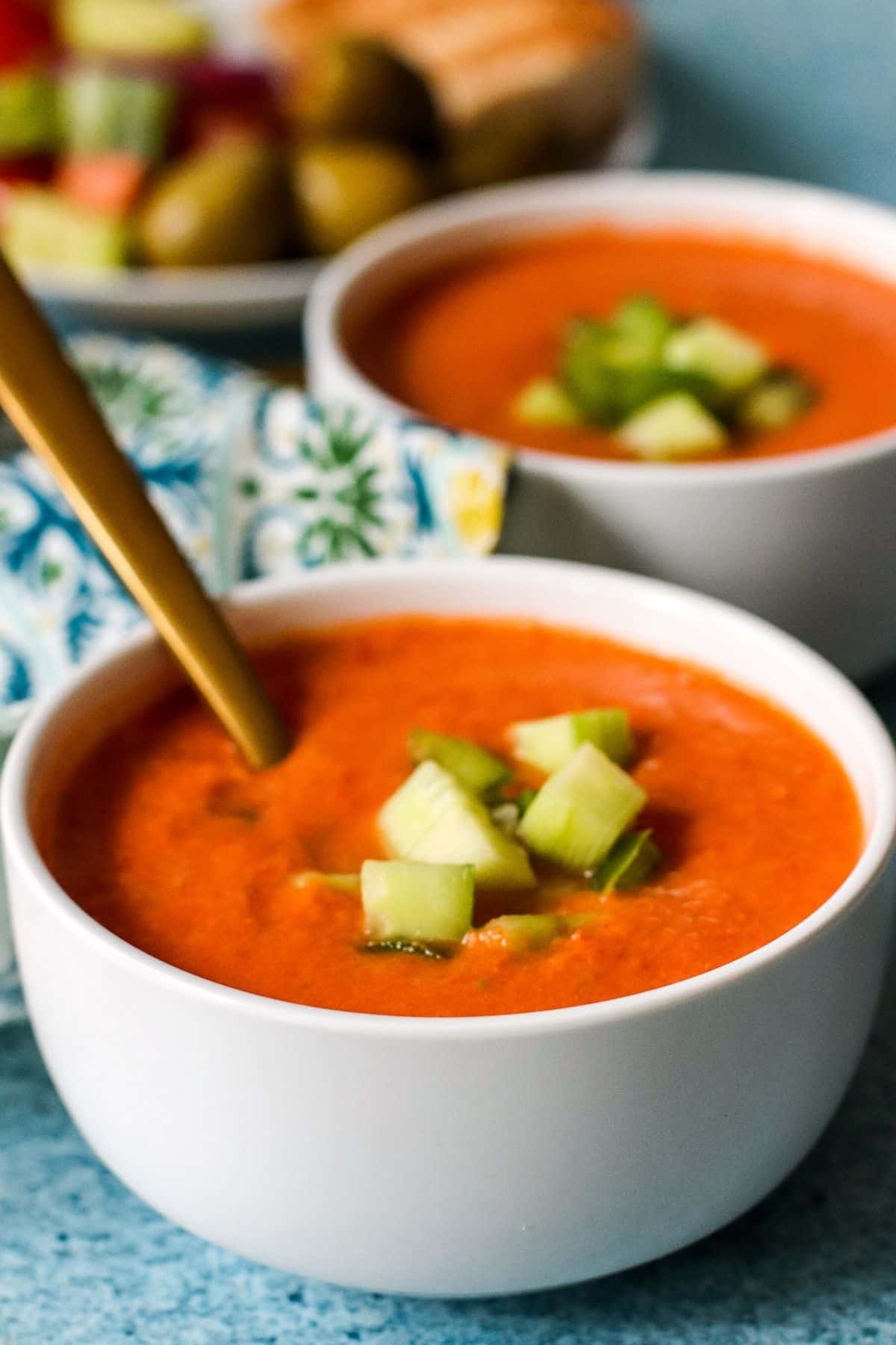 Bowls of gazpacho garnished with cubes of cucumber and green bell pepper