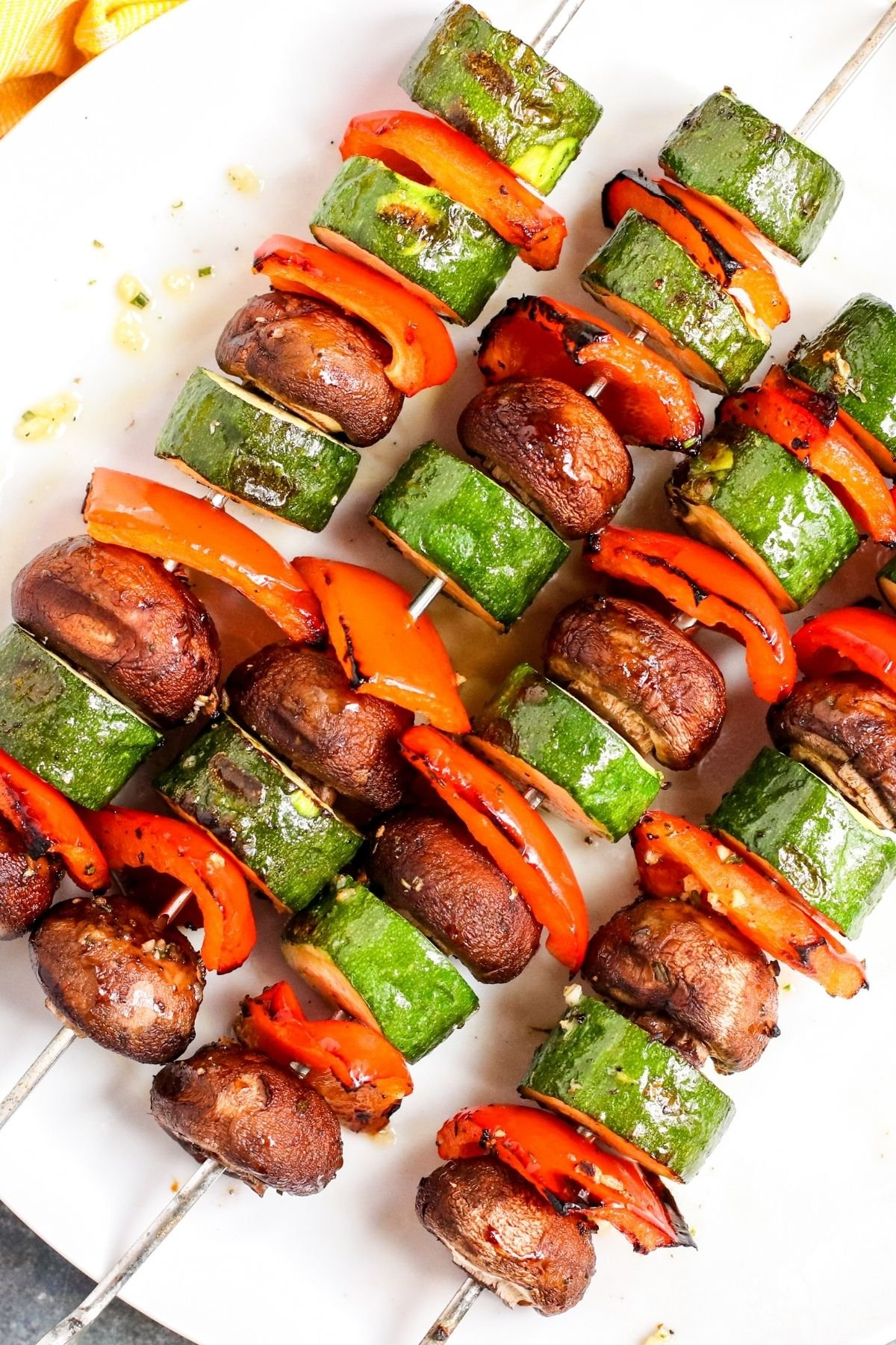 Platter of grilled zucchini, red bell peppers, and mushrooms on metal skewers