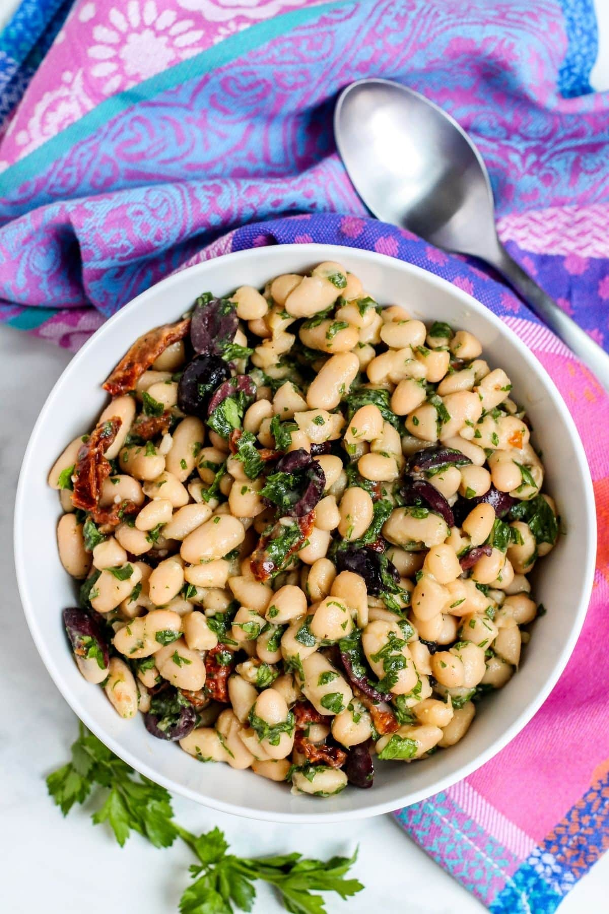 Bowl of salad with white beans, sun-dried tomatoes, olives, and parsley