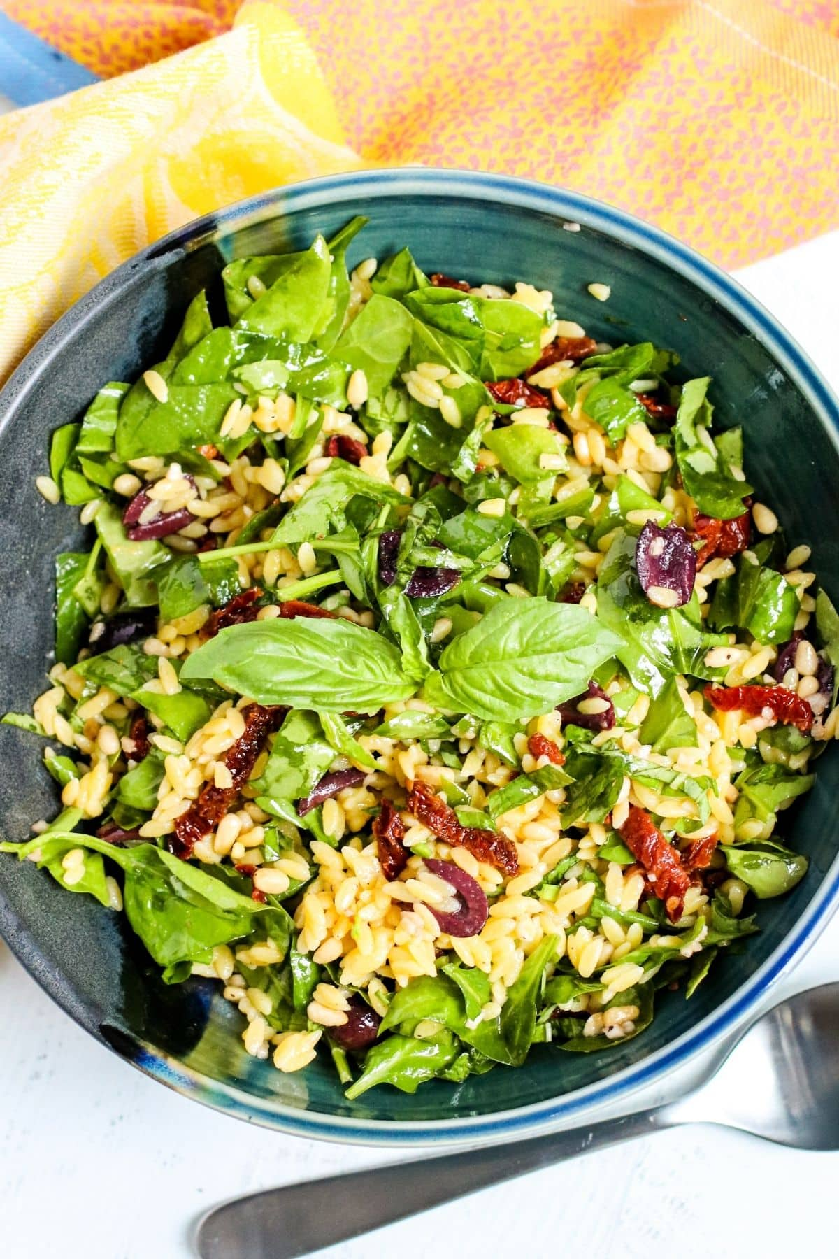 Bowl of spinach orzo salad with serving spoon
